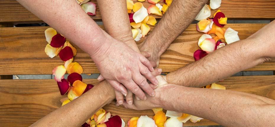 Dieses Foto zeigt viele Hände die aufeinander liegen und die Stärke des AWO-Verbandes symbolisieren sollen.